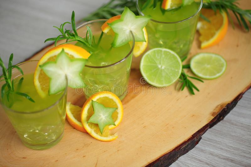 Three green cocktails standink on wood, decorated with orange, carambola, lime and rosemary. Ready to party stock photos