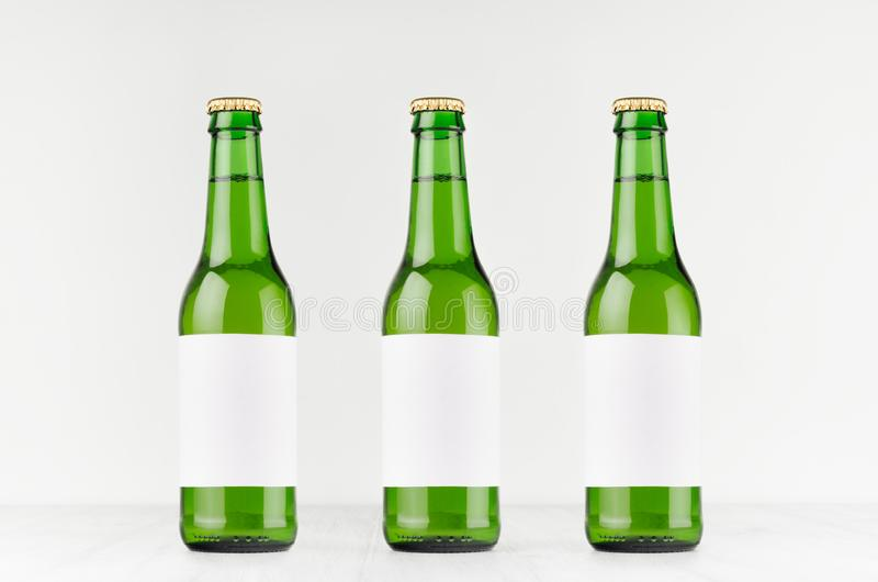 Three green longneck beer bottles 330ml with blank white label on white wooden board, mock up. Template for advertising, design, branding identity stock photo