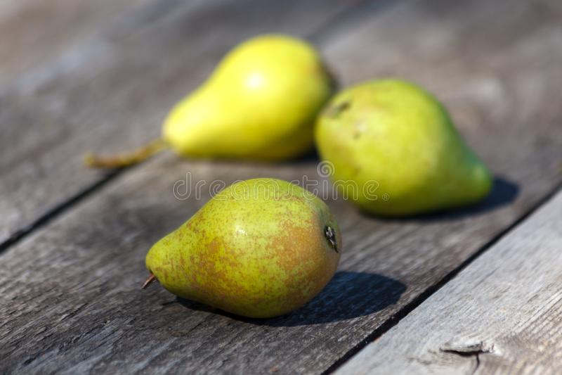 Three green pears on old grey wooden boards background royalty free stock photography