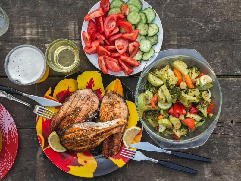 Three grilled salmon steaks with a side dish of baked vegetables stock photo