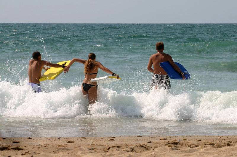 Three guys with bodyboard. Beach fun for three guy in the waves royalty free stock image
