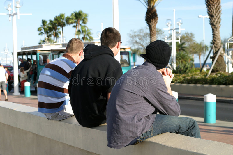 Three Guys on a Wall stock photos