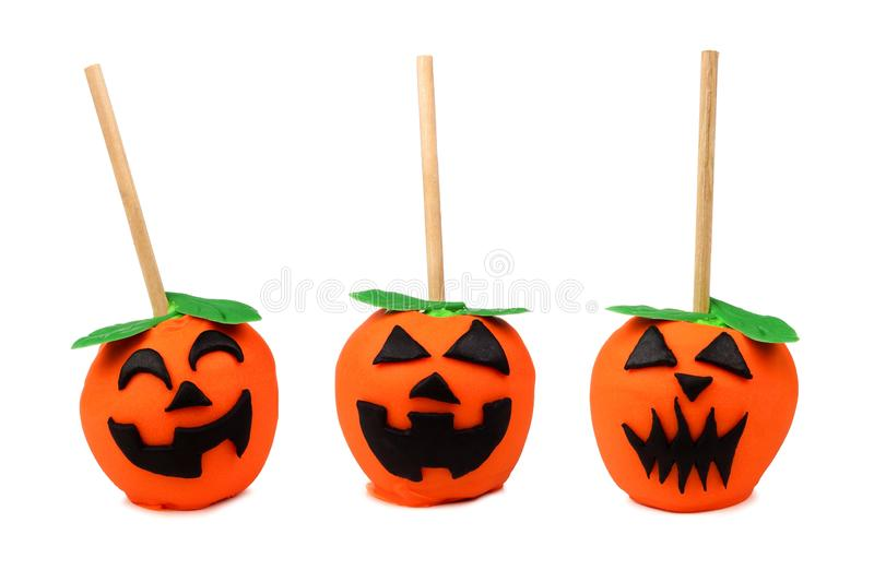 Three Halloween Jack o Lantern candy apples isolated on white royalty free stock photos