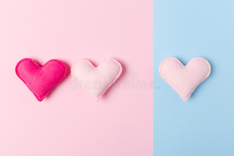 Three hand made felt hearts on pastel pink and blue background for love triangle, or infidelity concept. Three hand made felt hearts on pastel pink and blue stock photos