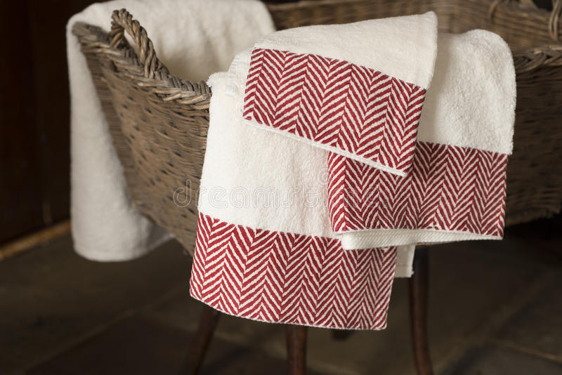 Three Hand Towels Hanging From Basket on Wooden Stool. Three white hand towels with maroon herringbone pattern on edges hanging from a woven rectangular basket royalty free stock photo