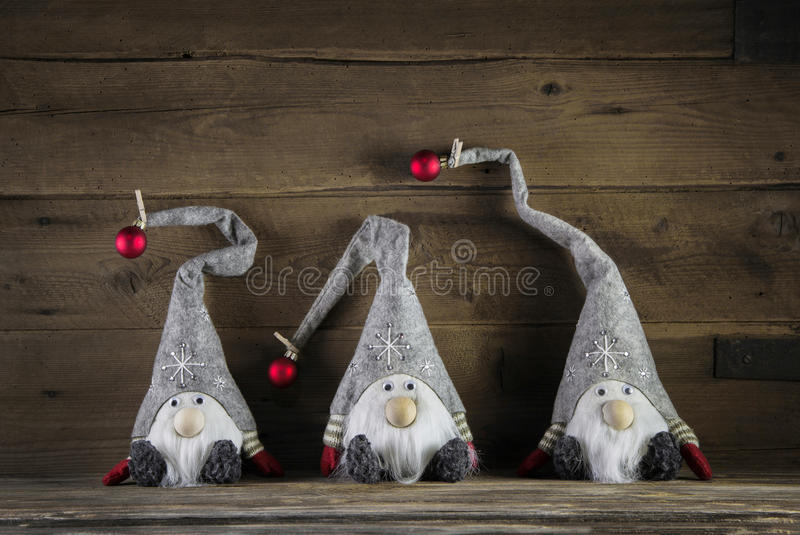 Three handmade imps on wooden background wearing santa hat for c stock image