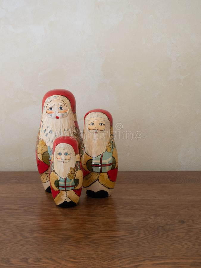 Three Handpainted Wooden Nesting Dolls Painted as Santa Claus. A family of three handpainted wooden Santa nesting dolls standing in a line holding gifts royalty free stock images