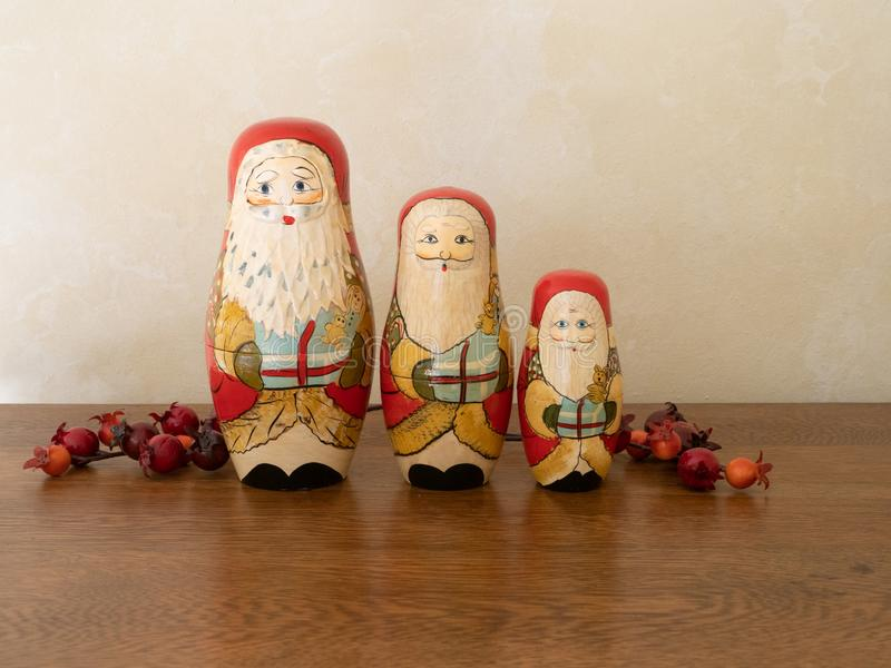 Three Handpainted Wooden Nesting Dolls Painted as Santa Claus in a Row. Three handpainted wooden Santa Claus nesting dolls holding gifts. Sitting on a wooden stock photography