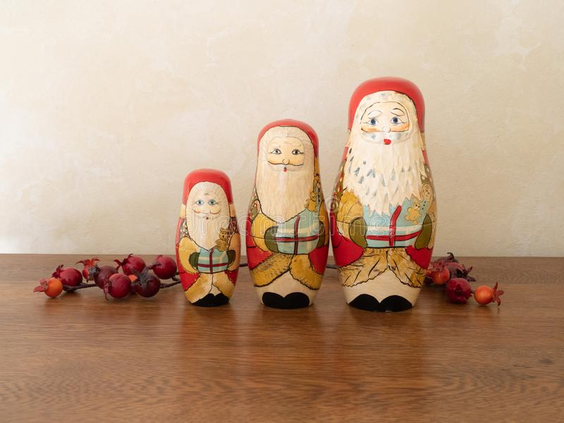 Three Handpainted Wooden Santa Claus Dolls with Red Berries. Three handpainted wooden Santa Claus nesting dolls holding gifts. Sitting on a wooden surface with royalty free stock images