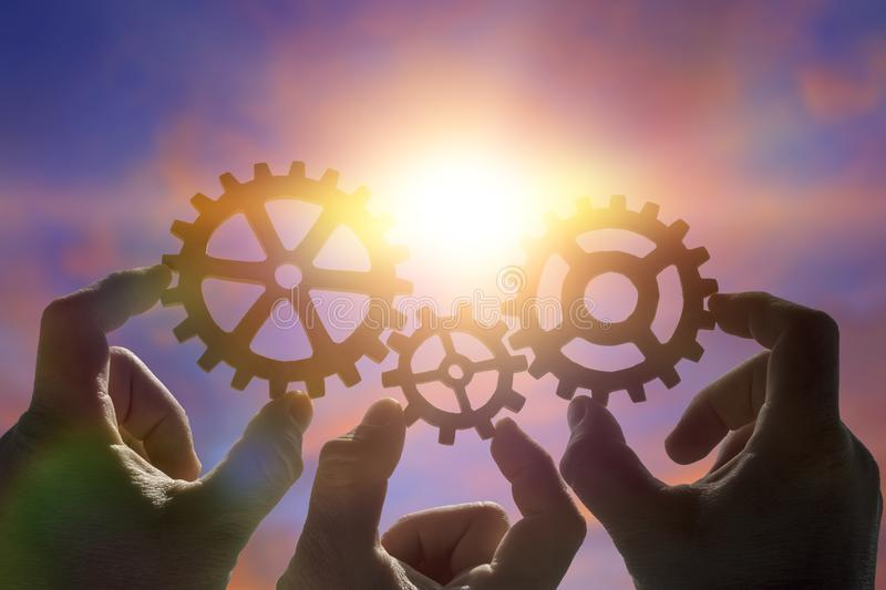 Three hands of businessmen collect the gear from the gears of the details of the puzzles. Against the background of sunlight. Concept business idea. Teamwork royalty free stock photography