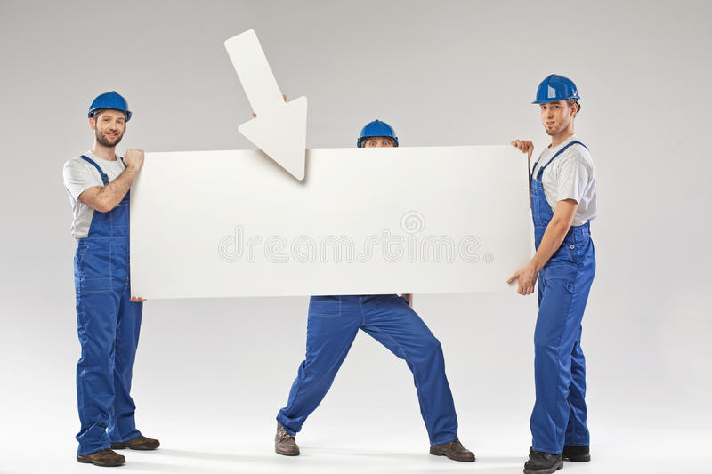 Three handsome builders holding a banner stock image