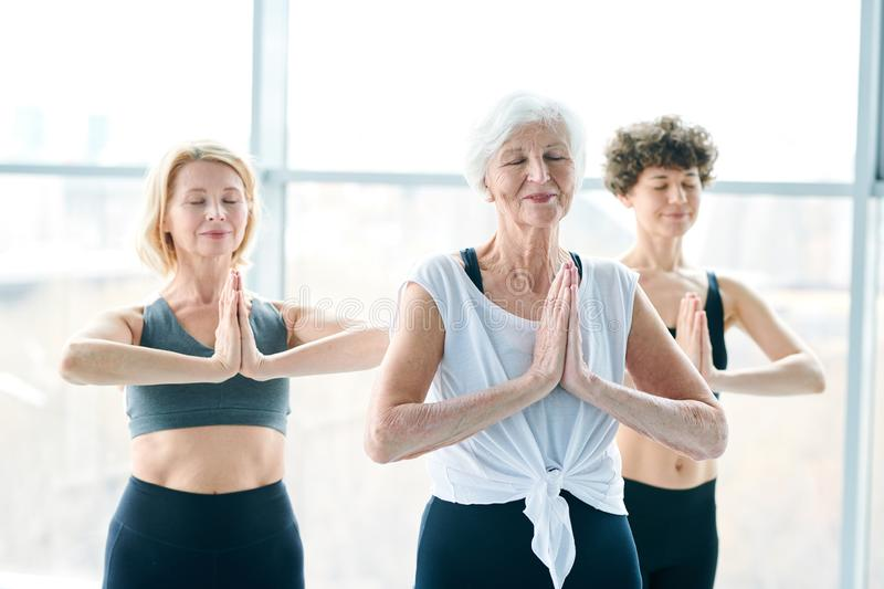 Yoga relaxing. Three happy active women in sportswear practicing relaxing yoga exercise with their hands put together by chest stock images