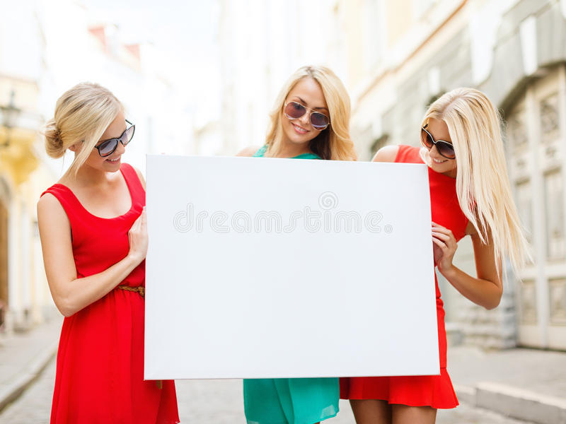 Three happy blonde women with blank white board stock images