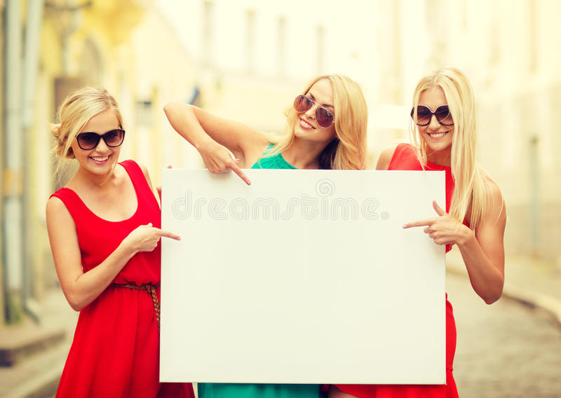 Three happy blonde women with blank white board royalty free stock photography