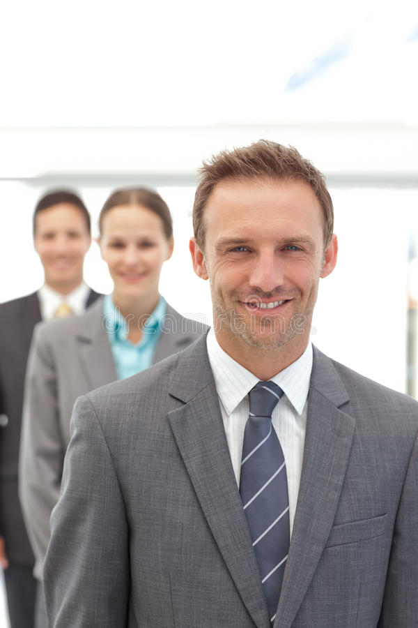 Three happy business people posing in a row. In the office royalty free stock image