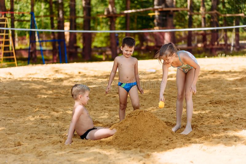 Three happy children in bathing suits bury their feet in the sand on the beach in summer stock photo