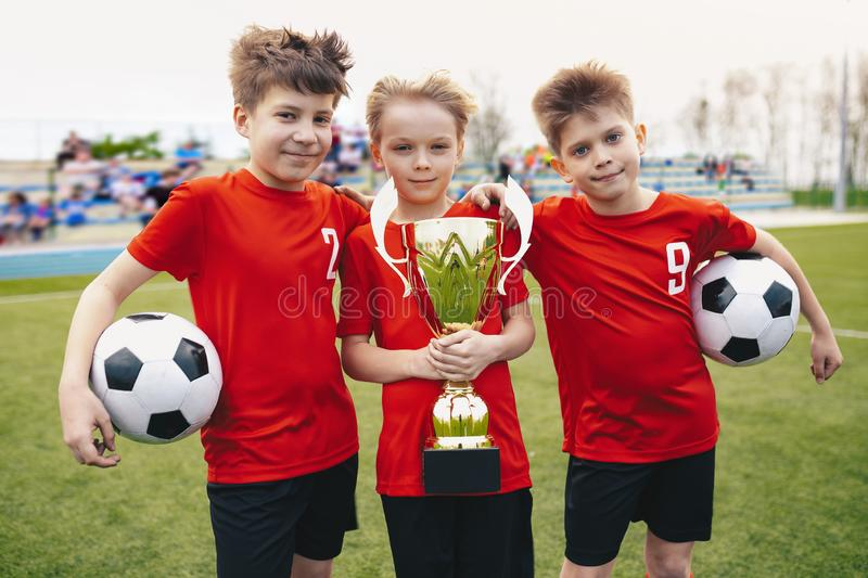 Three Happy Cheerful Kids of Sports Soccer Team. Boys Football Players Holding Trophy at the Stadium royalty free stock photos
