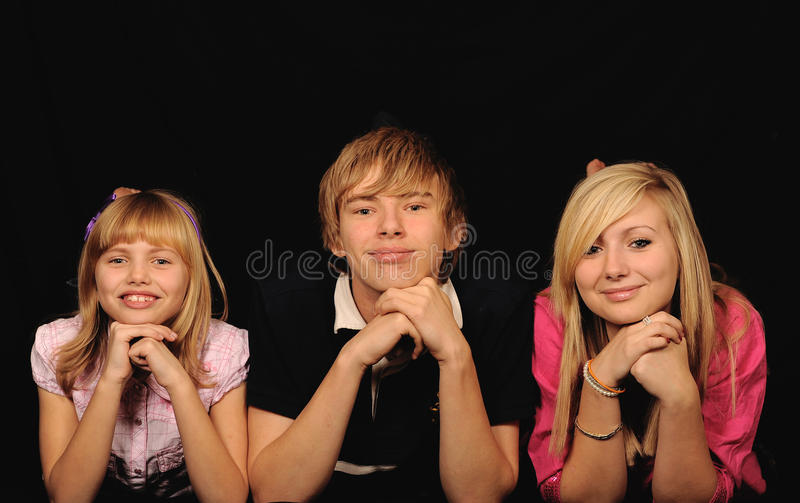 Three happy children. Happy adolescent boy with two young sisters, black studio background stock photography
