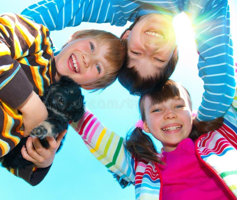 Three happy children. Circle of three happy children with their dog royalty free stock photo