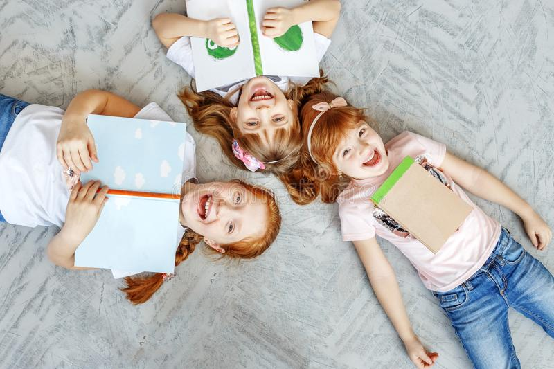 Three happy children lie on the floor and read books. The concep royalty free stock photos