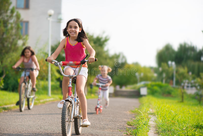 Three happy children riding on bicycle. And acooter royalty free stock photography
