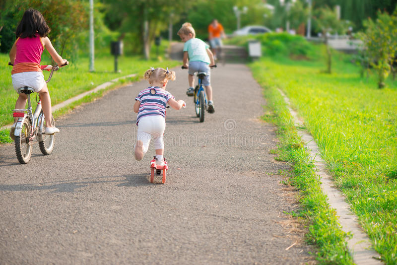 Three happy children riding on bicycle. And acooter royalty free stock image