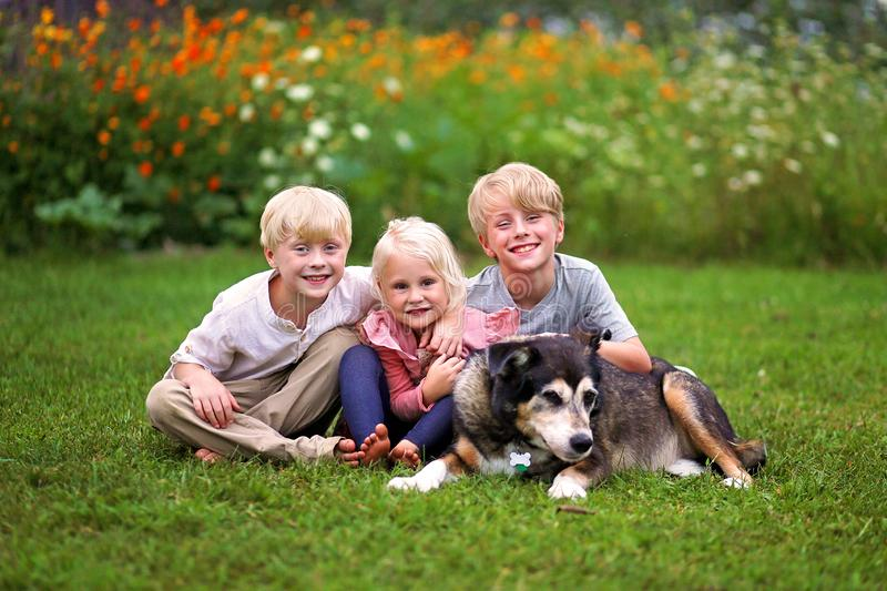 Three Happy Cute Little Kids Smiling OUtside with their Old Pet Dog royalty free stock photos