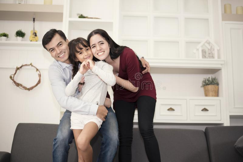 Three Happy family`s members in happy mood with hug, smiling togetherm Mom, Dad and daughter acting ing happiness concept royalty free stock photos