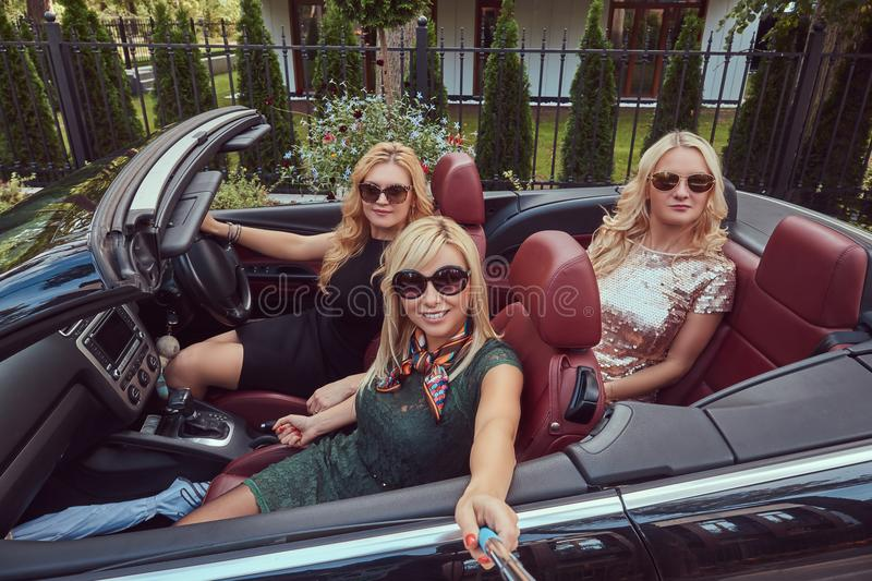 Three happy fashionable female friends take a selfie photo in luxury cabriolet car, during their trip vacation. Three happy fashionable female friends take a royalty free stock image