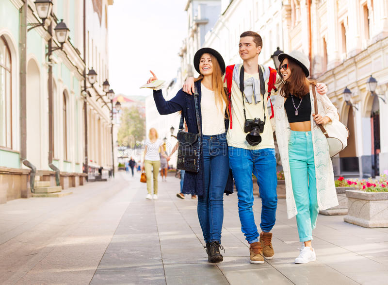 Three happy friends hugging in row and walking stock photos