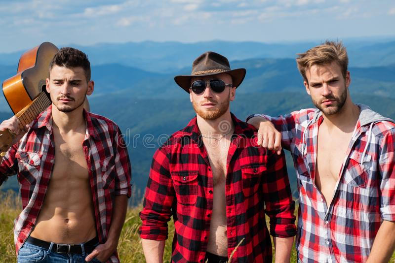 Three happy friends are looking on mountains and having fun together. Young people hiking in nature. Young people on stock photo
