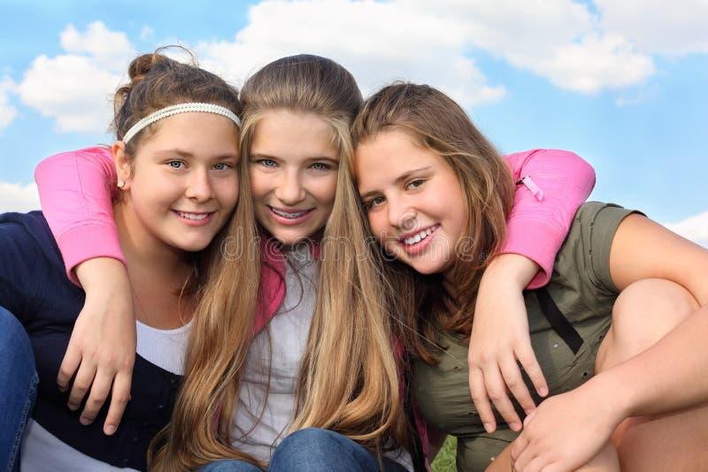 Three Happy Girls Hug At Background Of Sky Royalty Free Stock Image