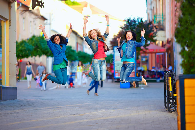 Three happy girls jumping on crowded city street. Three happy girls jumping on colorful crowded city street stock images
