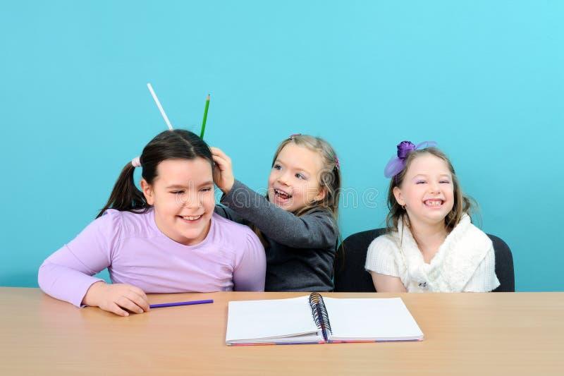 Three happy girls making jokes in school. Three happy school girls making jokes in classroom stock image