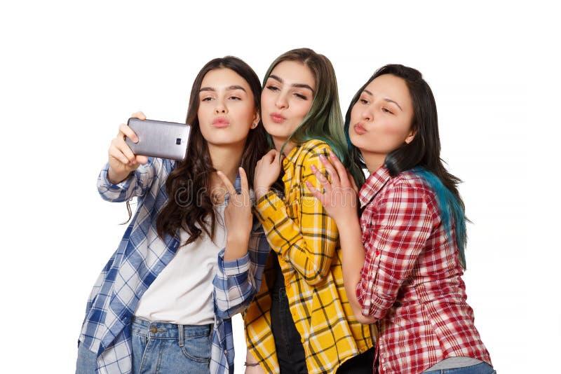 Three happy girls models make selfie. smiling. isolated on white background royalty free stock photo