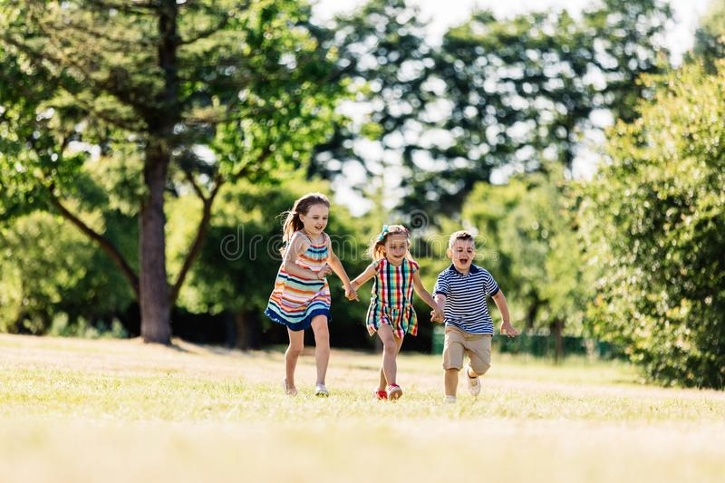 Three happy kids holding hands and running stock photography