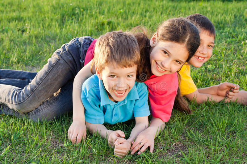 Three happy kids playing on the meadow royalty free stock photo