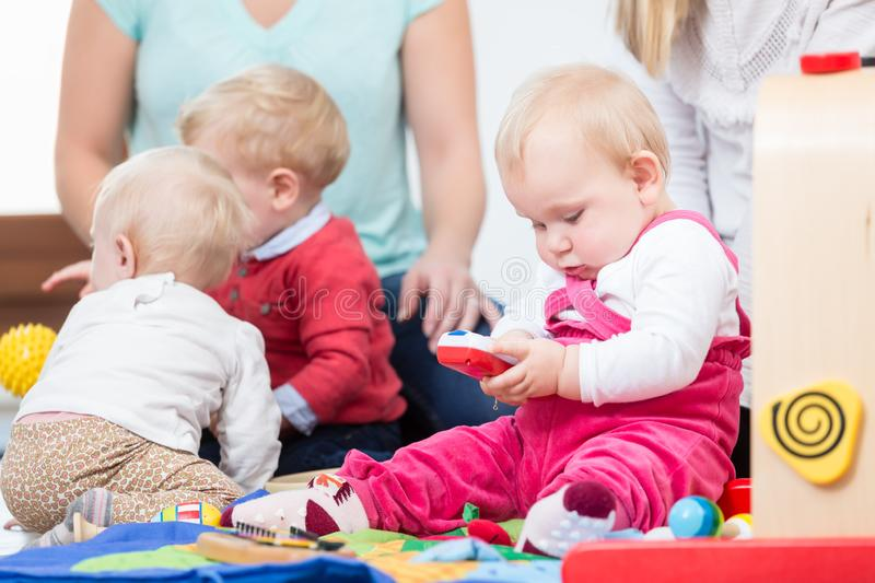 Three happy mothers watching their babies playing with safe multicolored toys stock image