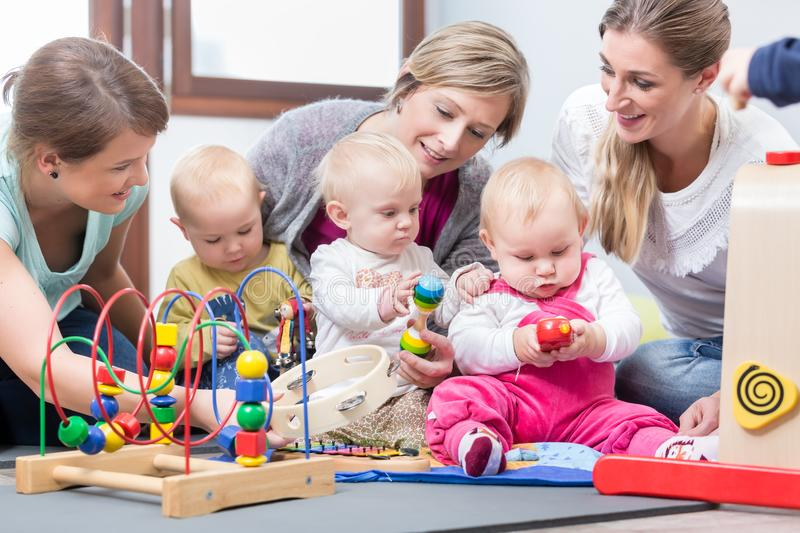 Three happy mothers watching their babies playing with safe toys royalty free stock photo