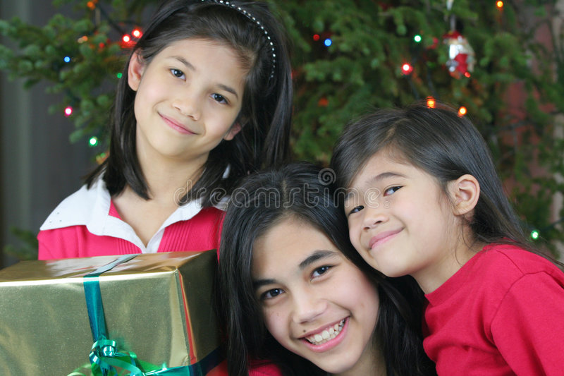 Three happy sisters with presents royalty free stock photography