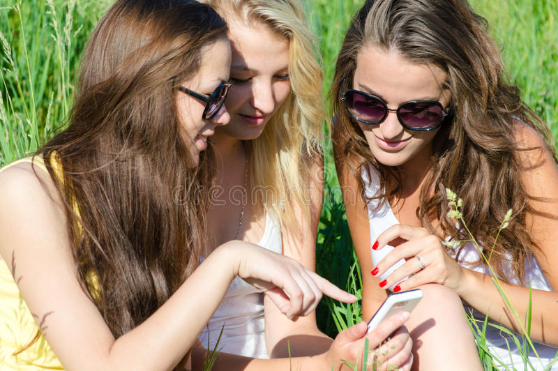 Three happy teen girl friends and mobile phone stock photo
