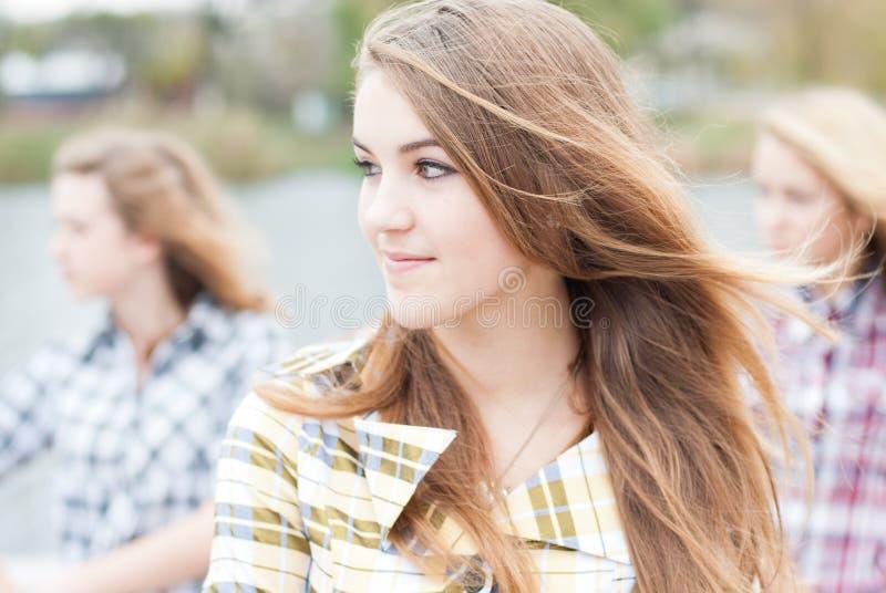 Three happy teen school girls friends outdoors royalty free stock image