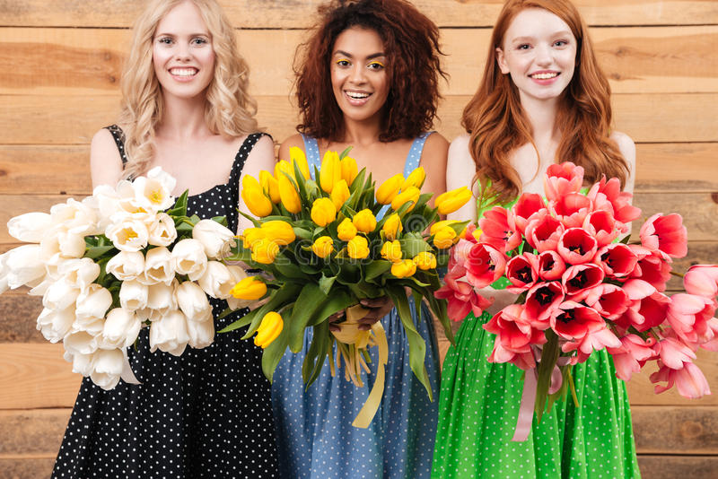 Three happy women holding bouquets of flowers stock images