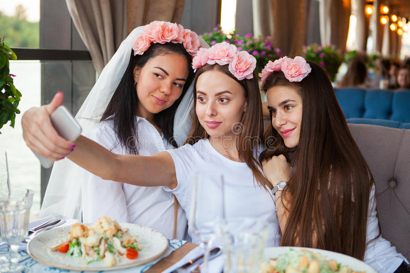 Three happy women taking selfie at hen party in cafe. Group happy women taking selfie at hen party in cafe stock photo