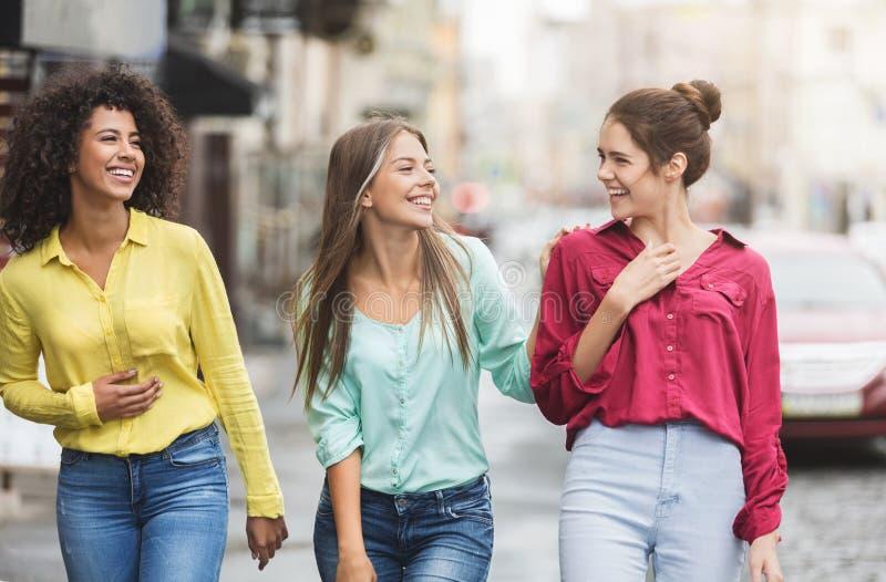 Three happy women walking in the city royalty free stock photos