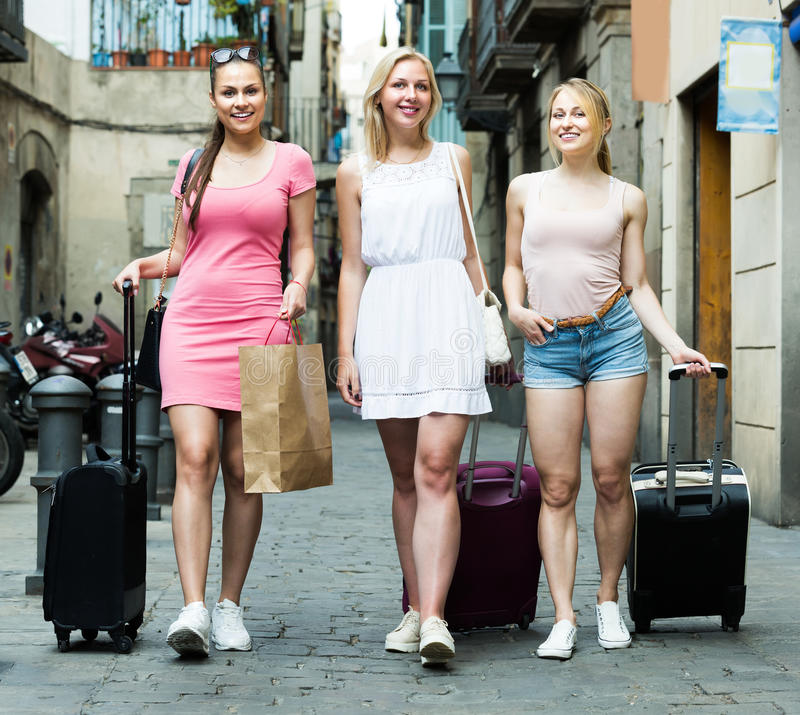 Three happy young girls tourists taking walk royalty free stock photo