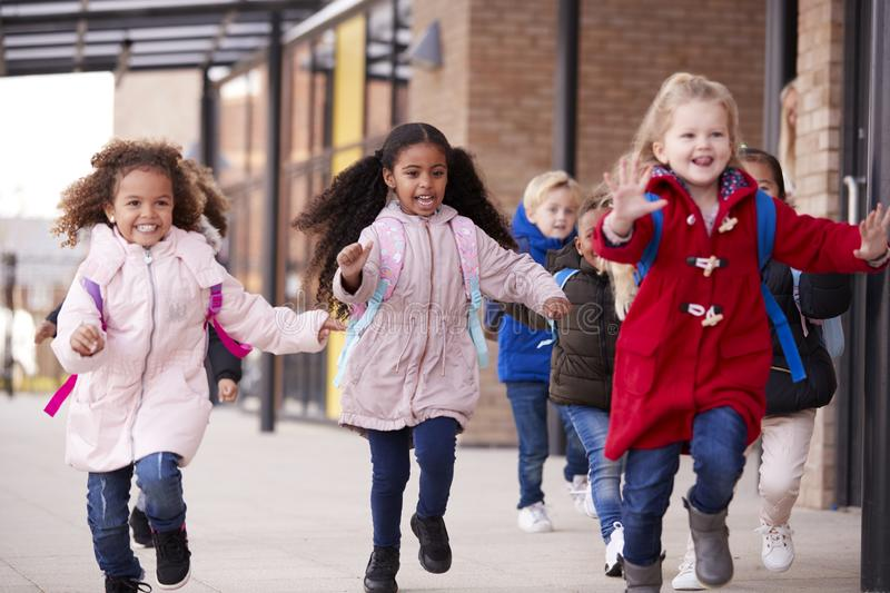Three happy young school girls wearing coats and carrying schoolbags running in a walkway with their classmates outside their infa royalty free stock image