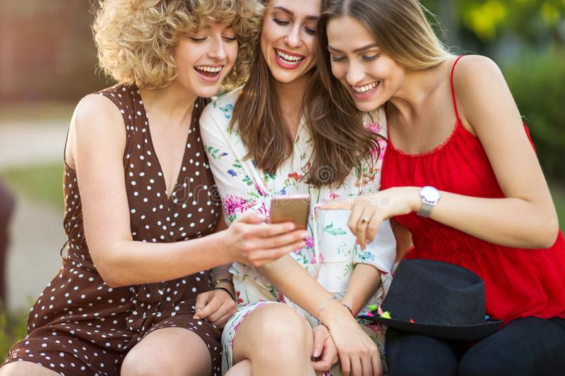 Three happy young women having fun with smart phone royalty free stock photo