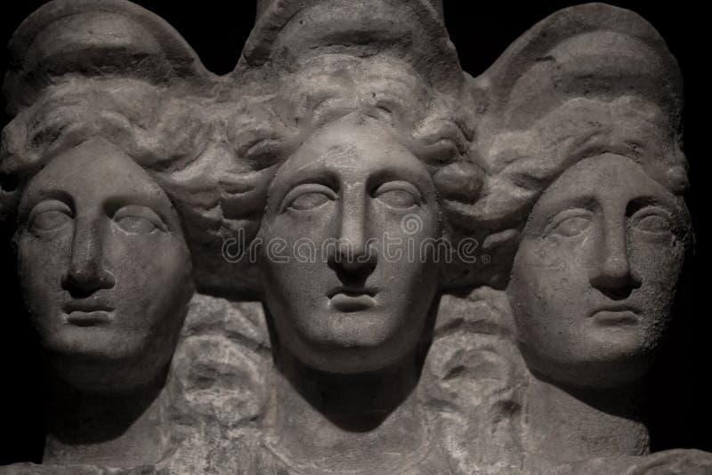Three headed roman-asian ancient statue of beautiful women at bl royalty free stock photo