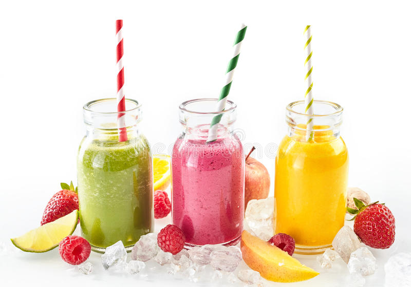 Three healthy smoothies with fresh tropical fruit. Including, strawberries, raspberry, orange, lime, mango and apple chilled on crushed ice and served in mason royalty free stock image
